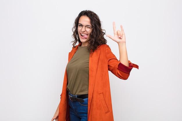 Mulher jovem e bonita se sentindo feliz, divertida, confiante, positiva e rebelde, fazendo sinal de rock ou heavy metal com a mão contra a parede branca Foto Premium