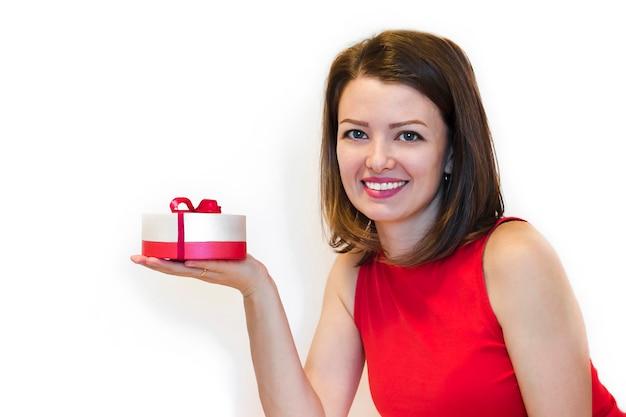 Mulher jovem e bonita, senhora, em roupas de férias vermelho com sorriso nevado, segurando uma caixa de presente. Foto Premium