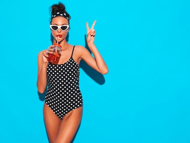 Mulher jovem e bonita sexy hipster sorridente em óculos de sol. garota de maiô de ervilhas de verão maiô. posando perto da parede azul, bebendo bebida smoozy cocktail fresca. mostra o sinal de paz Foto gratuita