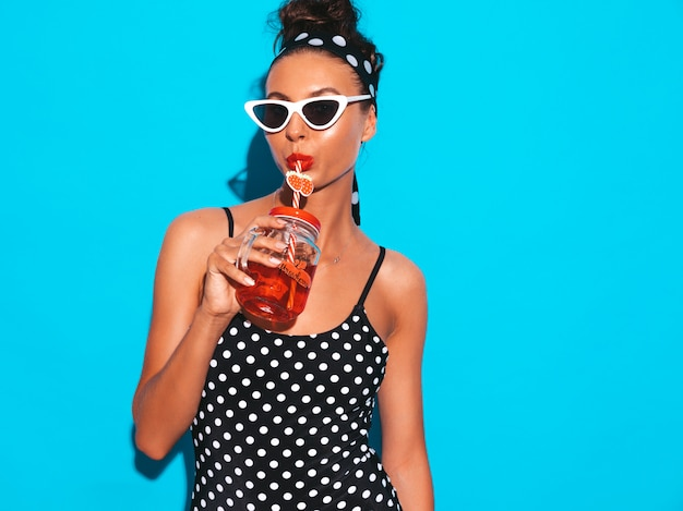 Mulher jovem e bonita sexy hipster sorridente em óculos de sol. garota de maiô de ervilhas de verão maiô. Foto gratuita