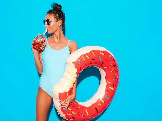 Mulher jovem e bonita sexy hipster sorridente em óculos de sol. garota em trajes de banho maiô verão com colchão inflável donut lilo. fêmea positiva enlouquecendo. posando perto da parede azul Foto gratuita