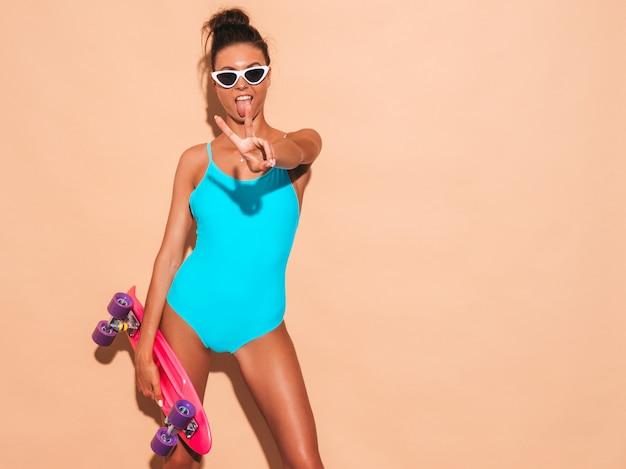 Mulher jovem e bonita sexy hipster sorridente em óculos de sol. menina na moda em trajes de banho de moda praia de verão. fêmea positiva enlouquecendo com skate centavo rosa, isolado na parede bege Foto gratuita