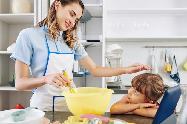 Mulher jovem e bonita sorridente, acariciando a cabeça da filha enquanto bate os ovos em uma grande tigela de plástico Foto Premium