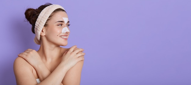 Mulher jovem e bonita sorridente com a pele limpa e perfeita olhando sonhadoramente para o lado e tocando seu ombro nu, fazendo procedimentos de beleza Foto gratuita