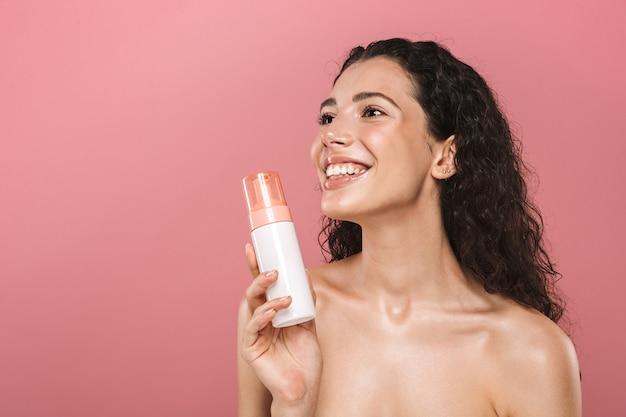 Mulher jovem e bonita sorridente posando isolada sobre uma parede rosa cuidar de sua pele segurando cosméticos. Foto Premium