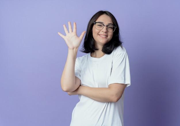 Mulher jovem e bonita sorridente usando óculos mostrando cinco com a mão Foto gratuita
