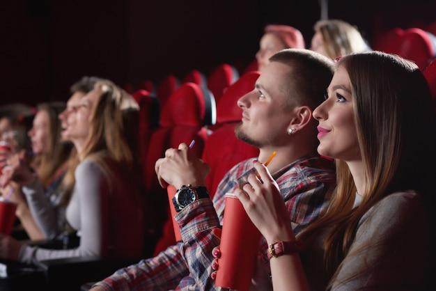 Mulher jovem e bonita sorrindo sentado ao lado de seu namorado no cinema. casal apaixonado, assistindo a um filme juntos, casais namorando pessoas amizade lazer divertido. Foto Premium