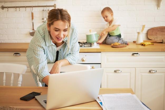 Mulher jovem e bonita tentando trabalhar usando o laptop e tomar conta de seu filho infantil. bebê fofo sentado no balcão da cozinha, brincando com uma panela, a mãe digitando no computador portátil em primeiro plano Foto gratuita