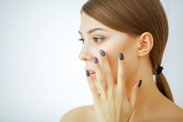 Mulher jovem e bonita tocando seu rosto limpo com uma pele fresca e saudável Foto Premium