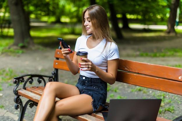 Mulher jovem e bonita usando laptop enquanto está sentado em um banco, bebendo a xícara de café para viagem Foto gratuita