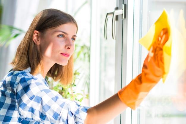 Mulher jovem e bonita usando luvas amarelas limpa o vidro da janela com guardanapo amarelo Foto gratuita