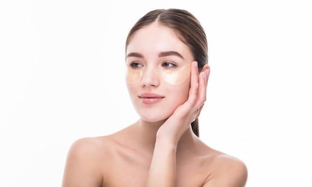 Mulher jovem e bonita usar patch no toque de pele fresca próprio rosto. tratamento facial. cosmetologia. Foto gratuita