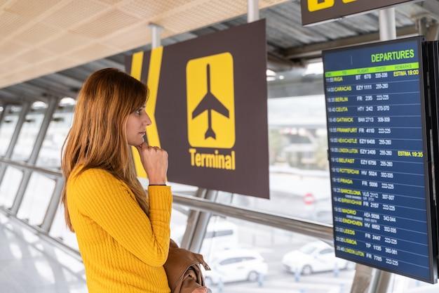 Mulher jovem e bonita verificando a hora de partida do seu voo nas placas de informações no aeroporto com sua bagagem Foto Premium