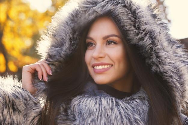 Mulher jovem e bonita vestindo um casaco com capuz de pele ao ar livre Foto Premium