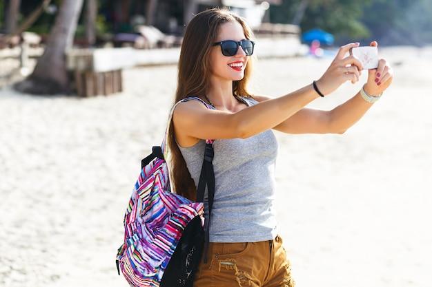 Mulher jovem e bonita viajante fazendo fotos na praia ensolarada, viajar sozinha com uma mochila no país tropical quente, roupa casual, corpo fitness, clima de aventura. Foto gratuita