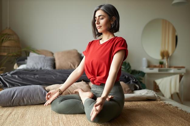 Mulher jovem e elegante de cabelos grisalhos praticando meditação em seu quarto, sentada na posição de lótus, fechando os olhos e fazendo gestos de mudra Foto gratuita