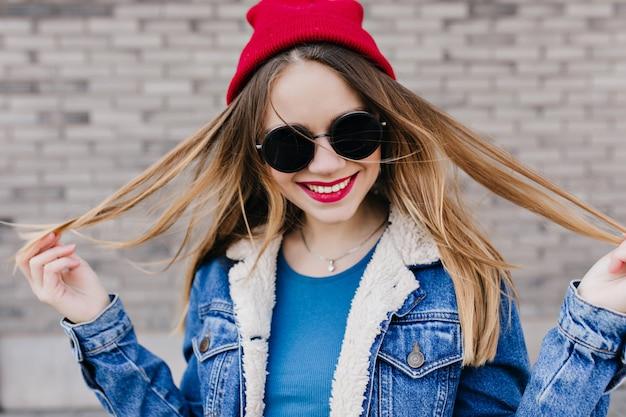 Mulher jovem e encantadora com maquiagem brilhante, passando o dia de primavera ao ar livre. foto de uma linda garota branca em uma jaqueta jeans rindo em frente a parede de tijolos. Foto gratuita