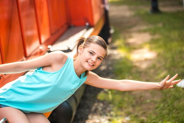 Mulher jovem e feliz, puxando o rosto para fora da porta do trem à procura de alguém na estação ferroviária Foto Premium