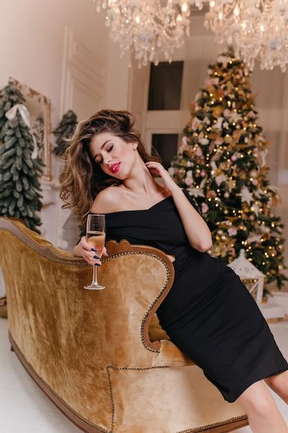 Mulher jovem e glamorosa, com belos cabelos penteados para o lado e com batom vermelho nos lábios, está sentada no sofá de veludo, tocando seu pescoço. Foto gratuita