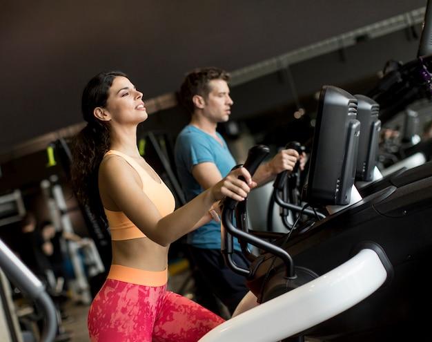 Mulher jovem, e, homem, ligado, elíptico, treinador deslizante, exercitar, em, ginásio Foto Premium