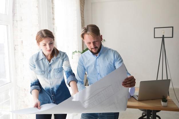Mulher jovem, e, homem, trabalhando, ligado, blueprint, em, escritório Foto gratuita