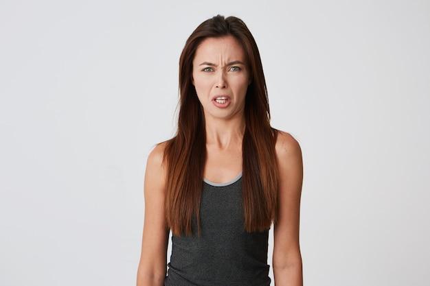 Mulher jovem e irritada com cabelo comprido parece zangada Foto gratuita