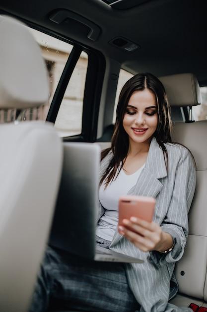 Mulher jovem e linda com laptop sentado no carro e falando ao telefone Foto gratuita