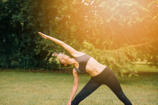 Mulher jovem e saudável de aquecimento ao ar livre no jardim Foto gratuita
