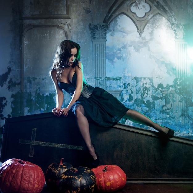 Mulher jovem e sexy, imagem de bruxas em um cemitério, sentado no caixão de tampa. Foto Premium