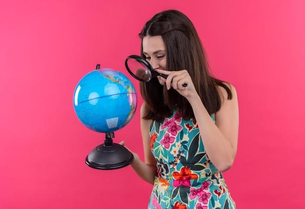 Mulher jovem e sorridente feliz segurando um globo terrestre e uma lupa na parede rosa isolada Foto gratuita