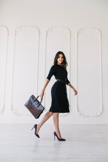 Mulher jovem elegante vestido com bolsa posando no quarto Foto gratuita
