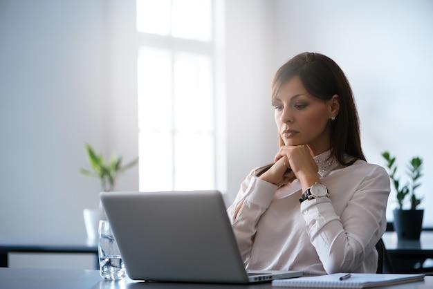 Mulher jovem, em, a, escritório, trabalhando, com, um, laptop Foto Premium