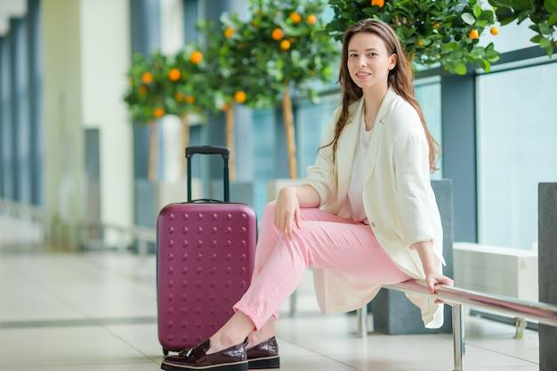 Mulher jovem, em, aeroporto internacional, com, dela, bagagem, e, café, ir, esperar, para, dela, vôo Foto Premium