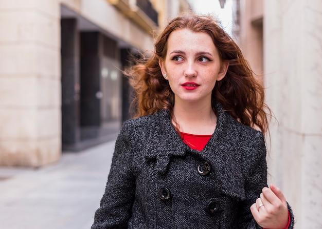 Mulher jovem, em, agasalho, andar, em, rua Foto gratuita