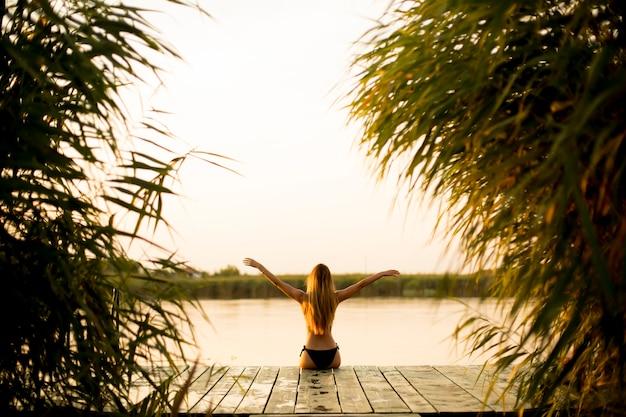 Mulher jovem, em, biquíni, ligado, cais, por, rio Foto Premium