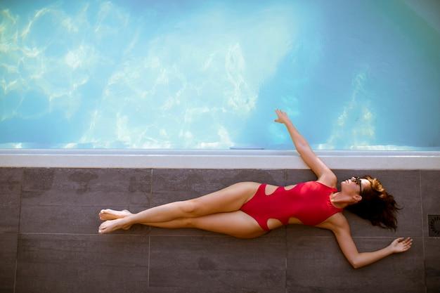 Mulher jovem, em, biquíni, posar, por, a, piscina, ao ar livre Foto Premium