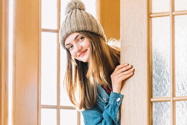 Mulher jovem, em, bobble, chapéu, espreitando, saída, de, porta Foto gratuita