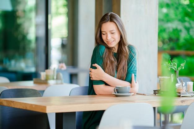 Mulher jovem, em, café ao ar livre Foto Premium