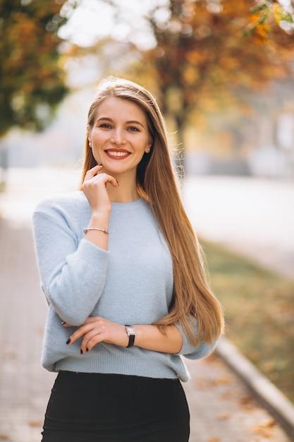 Mulher jovem, em, camisola azul, em, outono, parque Foto gratuita