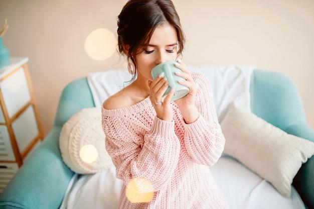 Mulher jovem em casa sentado na cadeira moderna em frente à janela, relaxando em sua sala de estar lendo livro e bebendo café ou chá Foto Premium