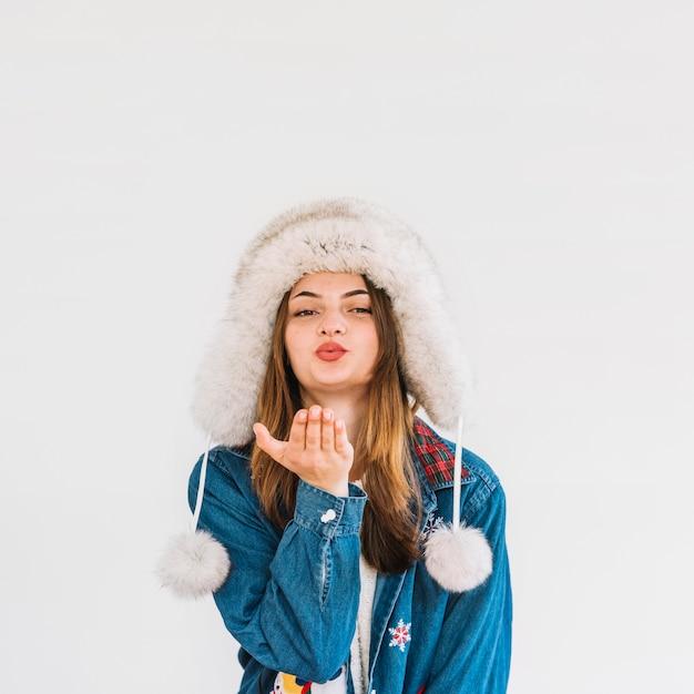 Mulher jovem, em, chapéu pele, enviando, ar, beijo Foto gratuita