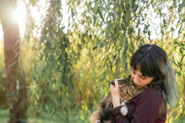 Mulher jovem, em, floresta, segurando, dela, adorável, gato tabby Foto gratuita