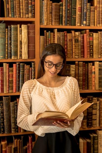 Mulher jovem, em, óculos, livro leitura, perto, prateleira Foto gratuita