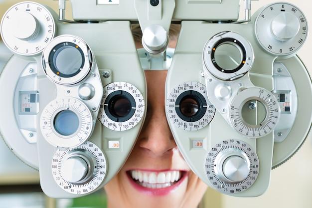 Mulher jovem, em, phoropter, para, teste olho Foto Premium