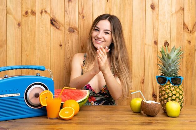 Mulher jovem, em, swimsuit, com, lotes, de, frutas, aplaudindo Foto Premium