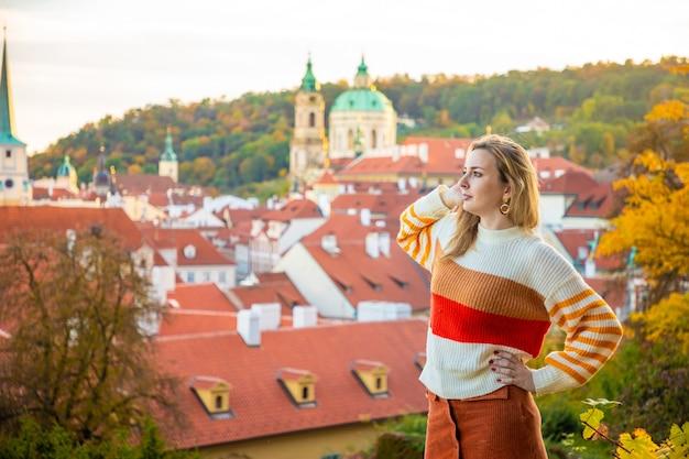 Mulher jovem em um telhado vermelho na cidade velha de praga, na república tcheca Foto Premium