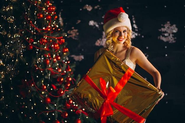 Mulher jovem, em, vestido, com, natal apresenta, por, árvore natal Foto gratuita