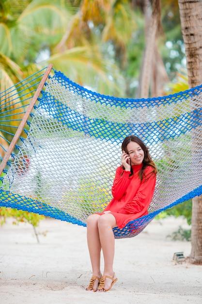 Mulher jovem, em, vestido vermelho, desfrutando, um, dia ensolarado, em, a, rede Foto Premium