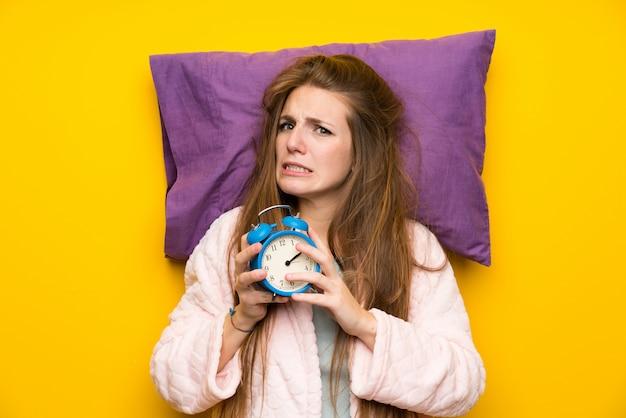 Mulher jovem, em, vestindo, vestido, em, um, cama, salientado, segurando, relógio vintage Foto Premium