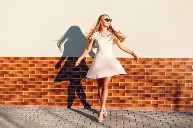 Mulher jovem engraçada com um sorriso e um vestido rosa se divertindo Foto Premium